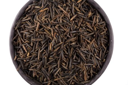 processed grains: Wild brown rice in bowl and loose over white background