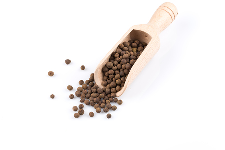 black peppercorn: Wooden shovel with large black peppercorn scattered from it