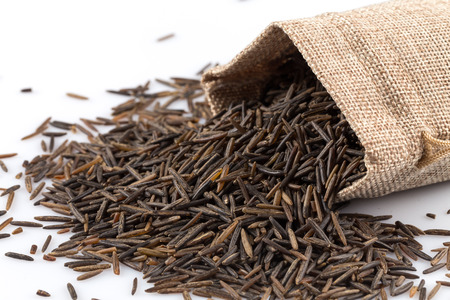 heap up: Close up image of a heap of wild rice on white background in a hessian sack