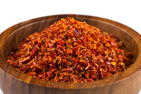 pepper flakes: Crushed red chili pepper in wooden bowl on white background