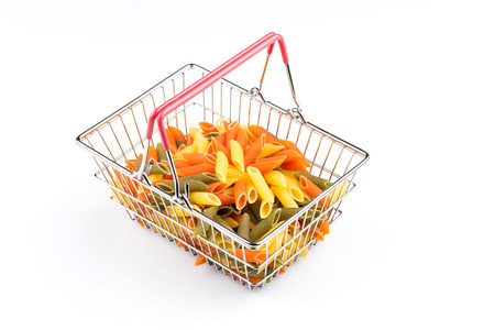 tri  color: Raw colored pasta in shopping basket isolated on white background. Tomato, spinach and wheat Stock Photo