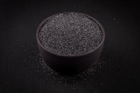 Mohn in einer Steinschale auf einem dunklen Hintergrund