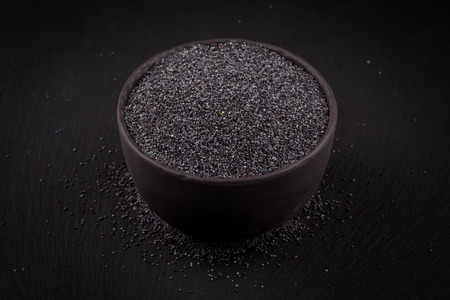 poppy seeds in a stone bowl on a dark background