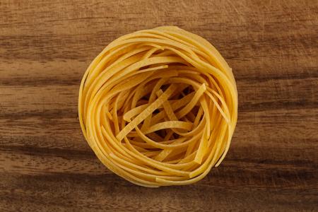 fettuccine: Fettuccine pasta nest on wooden background close up