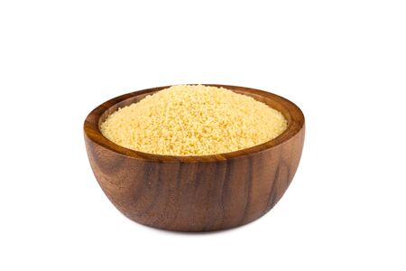 Raw couscous in a wooden bowl on white background