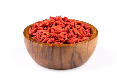 lycium: Chinese goji berries in wooden bowl close up on white background