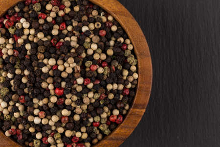 seeds of various: bowl of various pepper peppercorns seeds mix on black stone Stock Photo