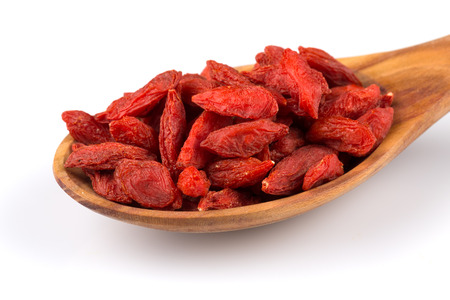 lycium: Chinese goji berries in wooden spoon close up on white background Stock Photo