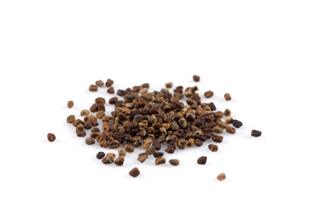 Decorticated cardamom seeds pile on a white background
