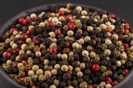 seeds of various: bowl of various pepper peppercorns seeds mix on dark stone