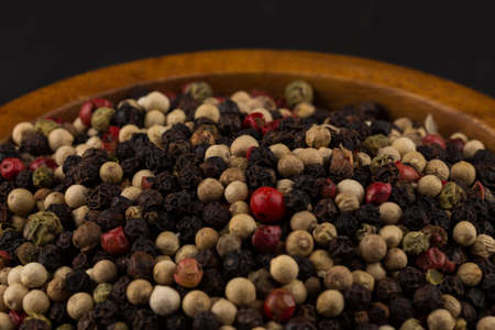 bowl of various pepper peppercorns seeds mix on black stone Stock Photo