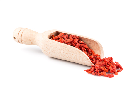 lycium: Chinese goji berries in wooden scoop close up on white background