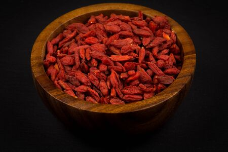 lycium: wooden bowl with goji berries on dark stone background Stock Photo