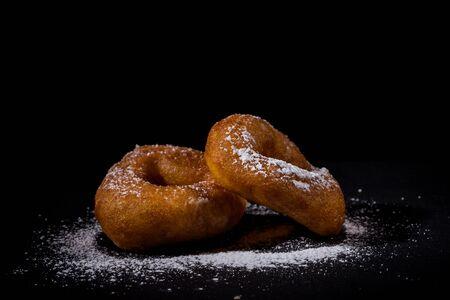 sprinkling: Sprinkling sugar powder on delicious homemade donut Stock Photo