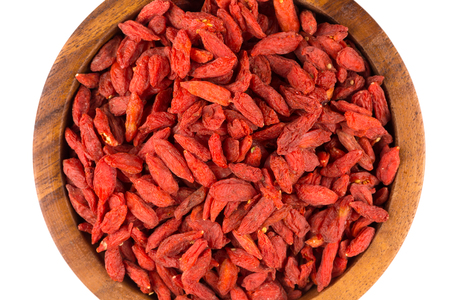 barbarum: Chinese goji berries in wooden bowl close up on white background