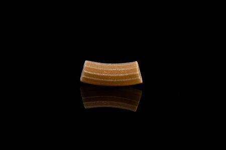 spelt: Close-up of wholegrain spelt pasta over black background