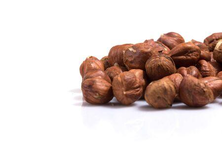 Heap of hazelnuts isolated on white background, macro image