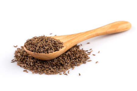 plant seed: Wooden spoon and pile of cumin seeds isolated on white background
