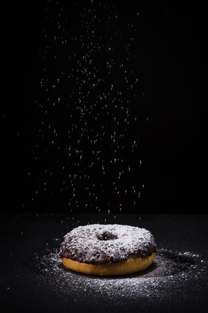 sprinkling: Sprinkling sugar powder on delicious donut topped with chocolate Stock Photo
