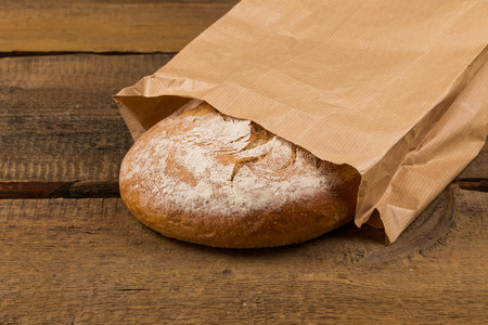 breadbasket: Delicious bread packed in paper on a wood table