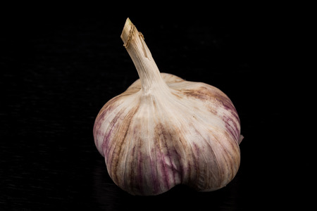 Garlic bulb closeup isolated on dark stone background