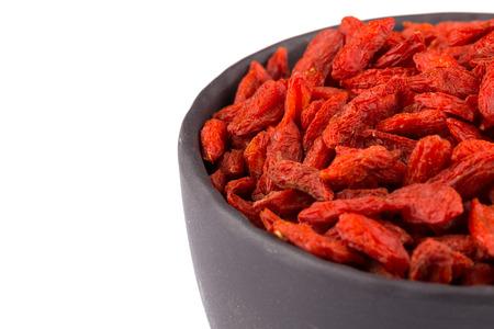 lycium: Chinese goji berries in dark stone bowl close up on white background Stock Photo