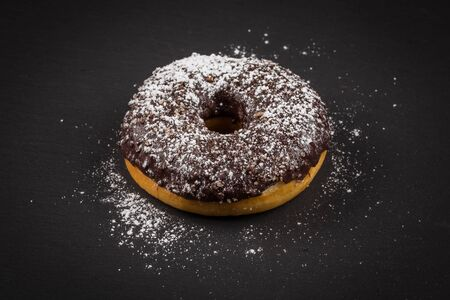 Sprinkling sugar powder on delicious donut topped with chocolate Stock Photo