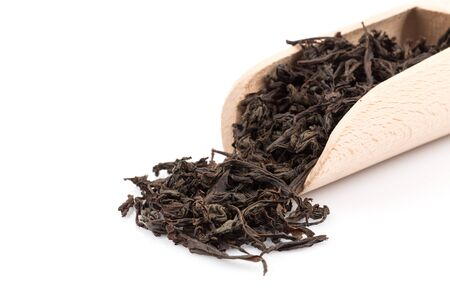 loose leaf: Black tea in a scoop on a black tea background. Close-up shot