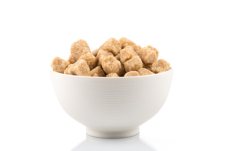 Brown cane sugar cubes in bowl on white