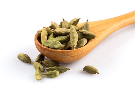 Cardamom in wooden spoon isolated on a white background