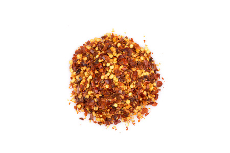 The pile of a crushed red pepper, dried chili flakes and seeds isolated on white background Stock Photo