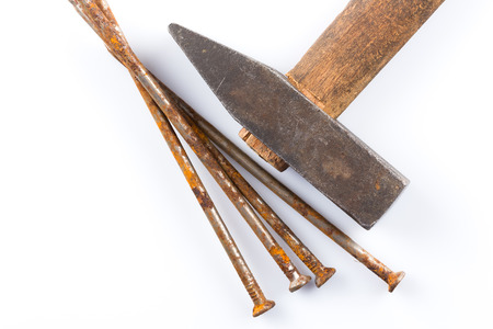 old hammer with wooden handle and some nails on white table Stock Photo