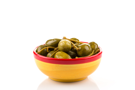 Bowl of canned capers on a white background