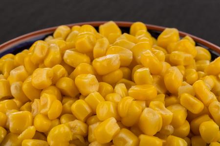 sweet canned corn in bowl on darl black stone slate board Stock Photo