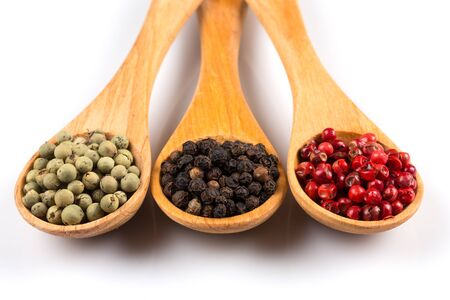 Wooden spoons with various pepper spice on white background Stock Photo