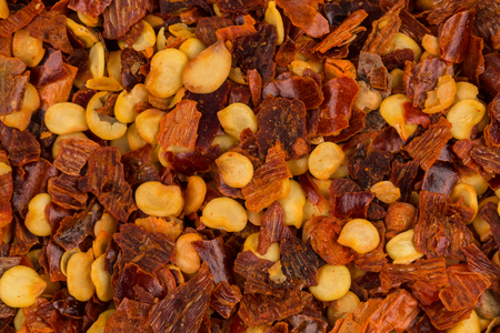 The pile of a crushed red pepper, dried chili flakes and seeds as a background