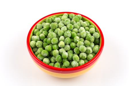 uncooked: Green frozen raw peas vegetable in a bowl on white background Stock Photo