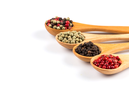 peppery: Wooden spoons with various pepper spice on white background Stock Photo