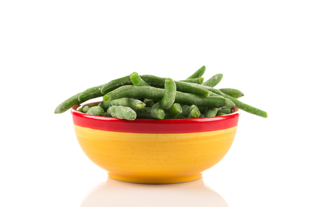 Frozen cut green beans vegetable in a bowl, isolated on white