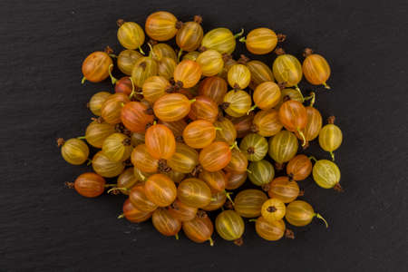 Fresh juicy gooseberry on stone dark background