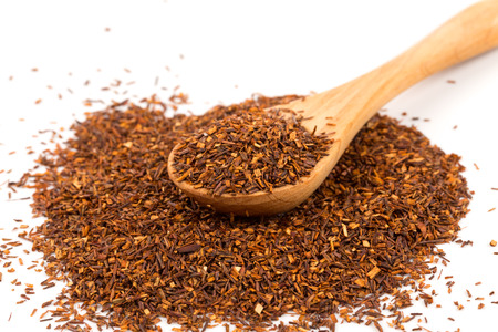 rooibos: Heap of red dry rooibos healthy traditional organic tea in spoon on white isolated background Stock Photo