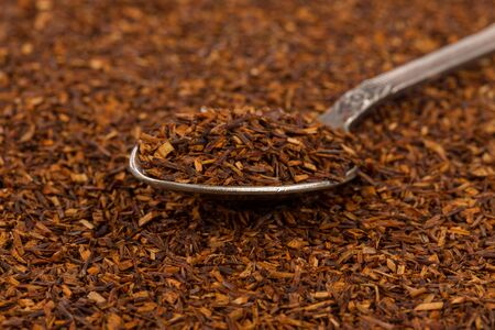 Dry rooibos healthy traditional organic tea close up in spoon