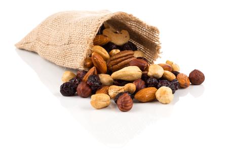 Meng noten, droge vruchten en druiven op een witte achtergrond in hessian tas