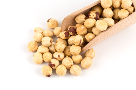 Closeup view of hazelnuts nuts pile on white background in wooden scoop
