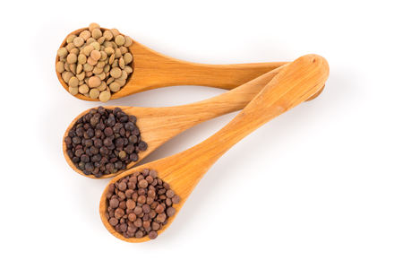 lenteja: Various lentils in wooden spoons isolated on white background.