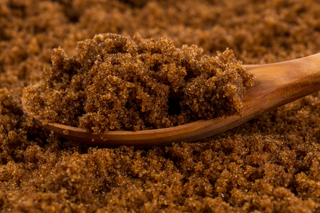 molasses: brown muscovado sugar in wooden spoon on the sugar background
