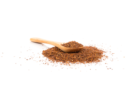 Heap of red dry rooibos healthy traditional organic tea in spoon on white isolated background Stock Photo