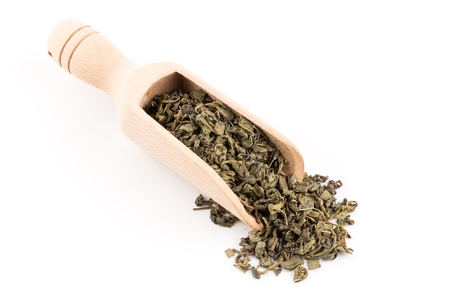 Gunpowder green tea in scoop isolated on a white background
