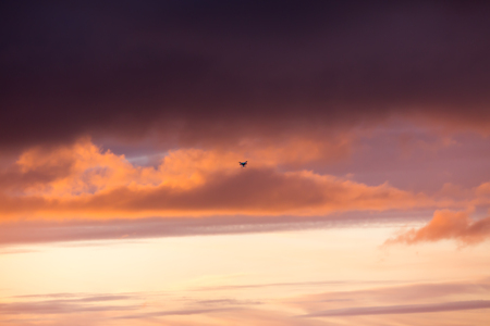 Silhouette of a flying drone in clouds sky on a background of sea sunset