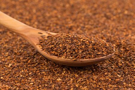 Heap of red dry rooibos healthy traditional organic tea in spoon